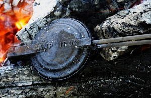 Bush pies being made in a bush pie iron on a hot bed of coals