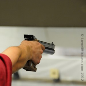 close-up of hand shooting air pistol at 10m target